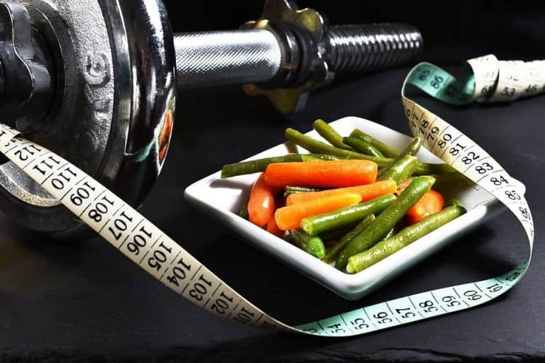 Veggies on plate, weights and measuring tape