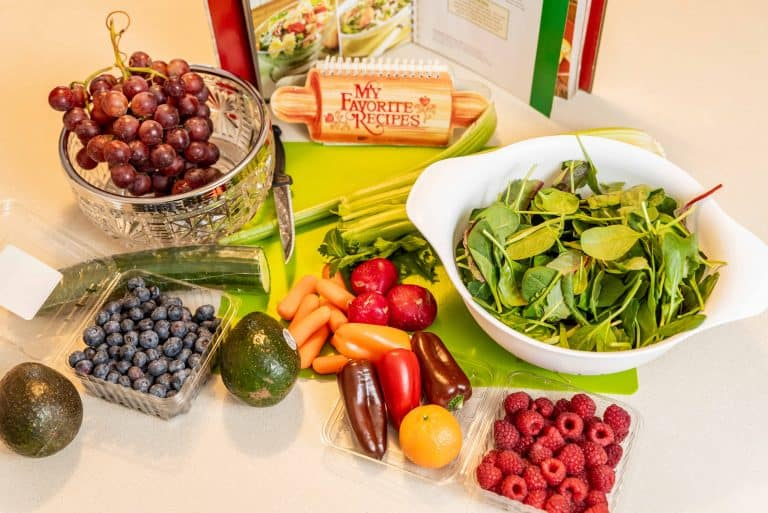 Variety of fruit and vegetables on table with cook book